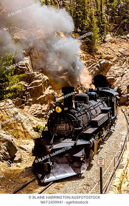 The Cumbres & Toltec Scenic Railroad train pulled by a steam locomotive comes out of a tunnel at 9669 feet on the 64 mile run between Antonito