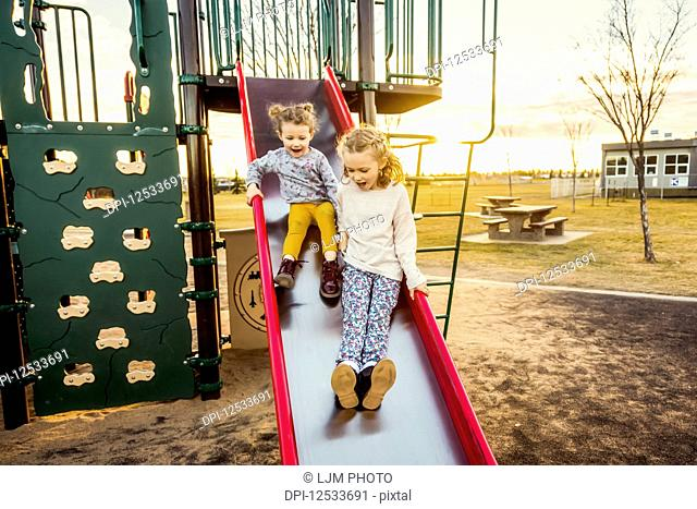 Two young sisters going down a slide in a playground on a warm autumn evening at sunset; Edmonton, Alberta, Canada