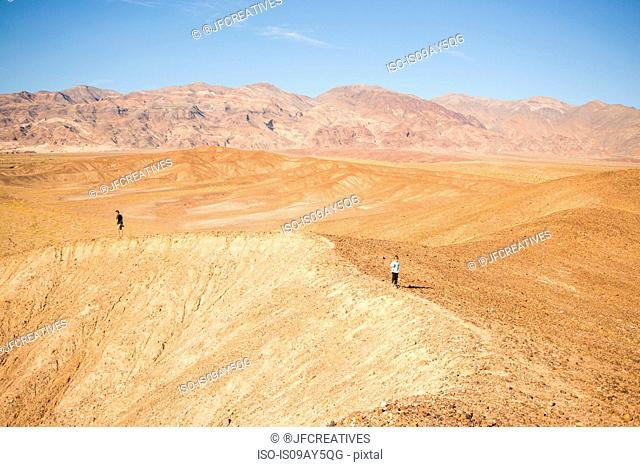 Man and boy exploring rim in desert, Olancha, California, USA
