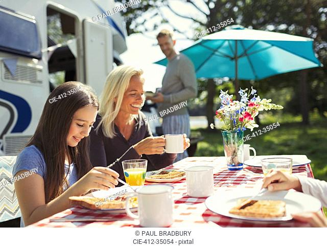 Smiling mother and daughter enjoying breakfast outside sunny motor home