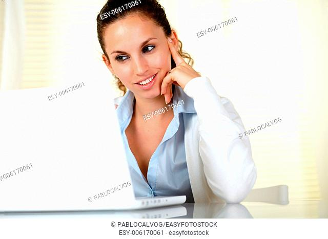 Pensive attractive young woman using her laptop at office - copyspace