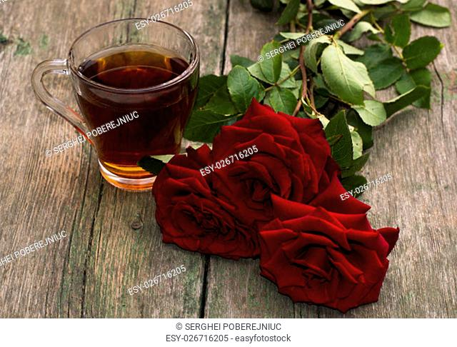 cup of tea and bright red roses on a wooden background, a still life, a subject beautiful flowers and drinks