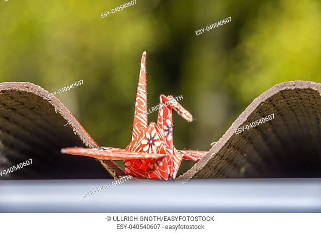 Origami paper crane made of original Japanese origami paper set up in a natural garden environment