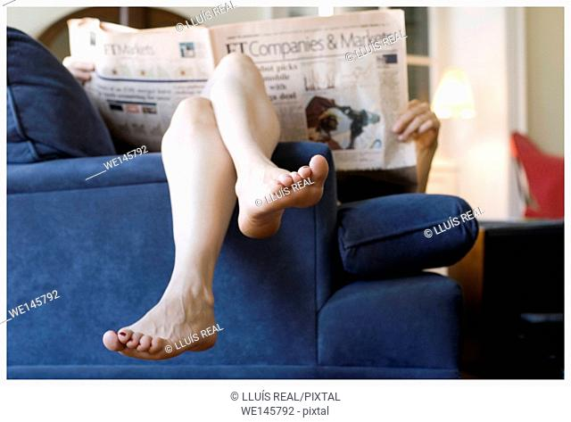 Young woman lying on a blue sofa, barefoot and in a relax position, reading a newspaper of Companies&Markets