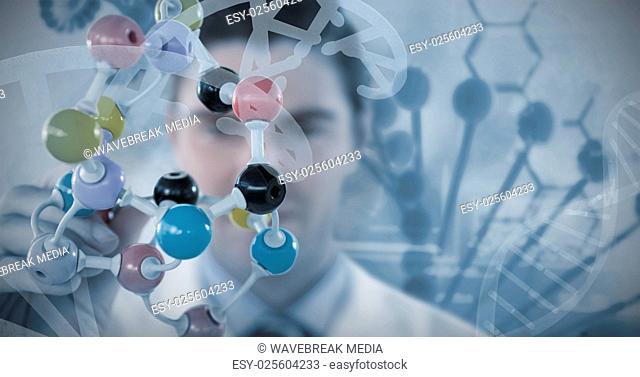 Composite image of scientist holding multi colored molecule structure