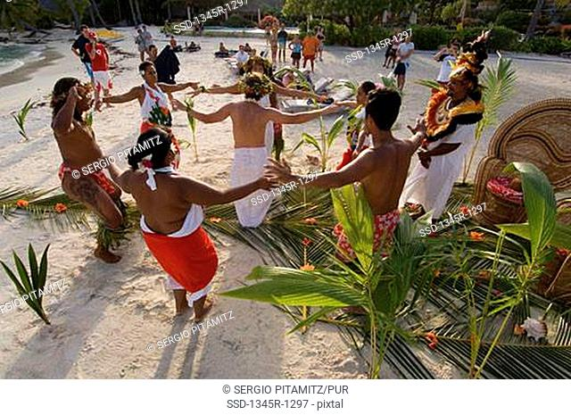 High angle view of a group of people dancing in a traditional wedding ceremony on the beach, Pearl Beach Resort, Bora Bora, French Polynesia