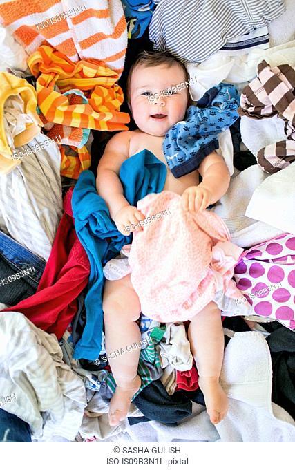 Baby girl lying on laundry