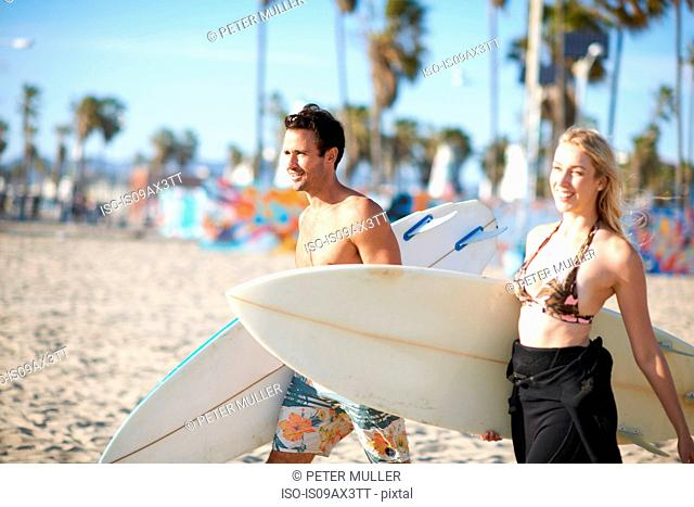Surfing couple carrying surfboards on Venice Beach, California, USA