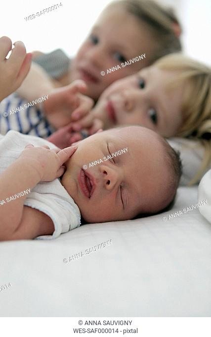Portrait of newborn baby boy and his two sisters in the background