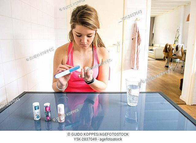 Tilburg, Netherlands. Young adult girly woman doing her nales, while sitting at her kitchen table