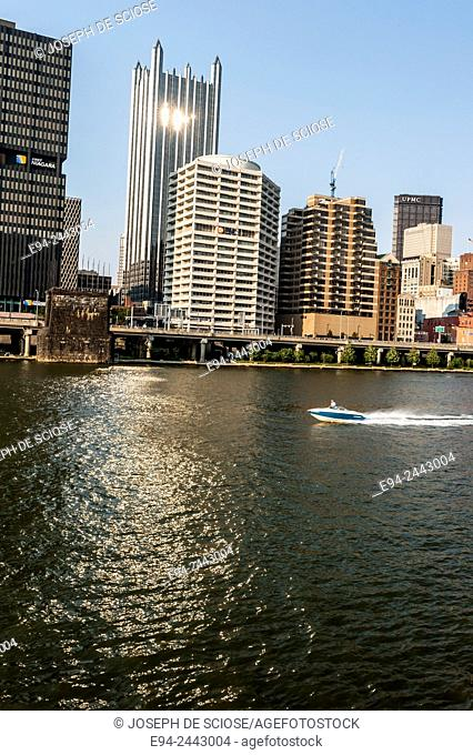 The Monongahela River with a partial view of the city of Pittsburgh and a motor boat on the water