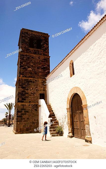Woman walking near the de Nuestra Senora de la Candelaria Church with its lava stone bell tower, La Oliva, Fuerteventura, Spain, Europe