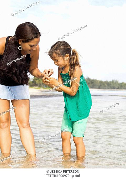 Girl (6-7) with mother walking in sea