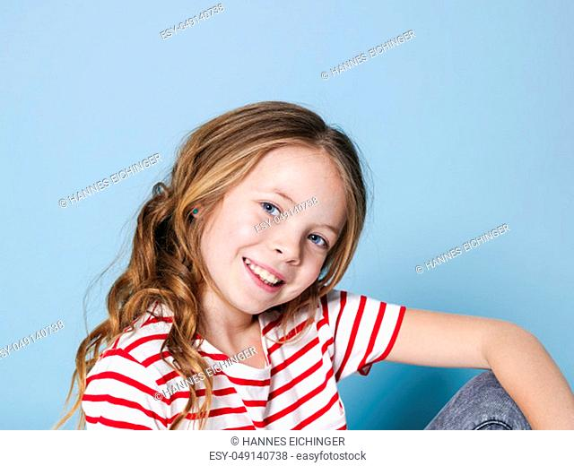 pretty girl with curly hair and red white striped shirt is posing in front of blue background