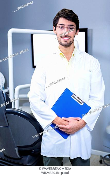Portrait of smiling dentist standing with a clipboard