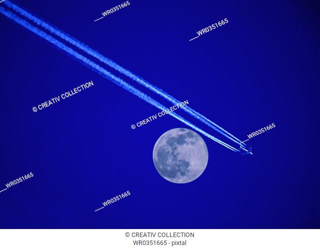 airplane in front of the moon on a purple blue sky