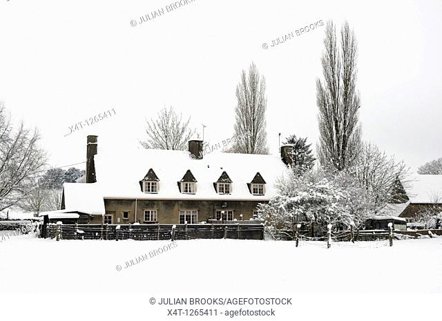 A row of tied cottages in the snow  Tackley in the Cotswolds