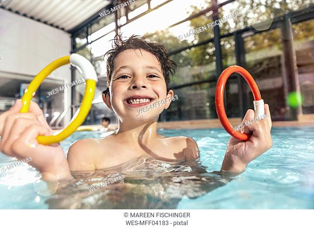 Portrait of proud boy holding two diving rings in swimming pool