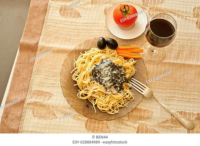 Pasta with sauce, parmesan cheese, black olives and spicy peppered carrots and a glass of wine