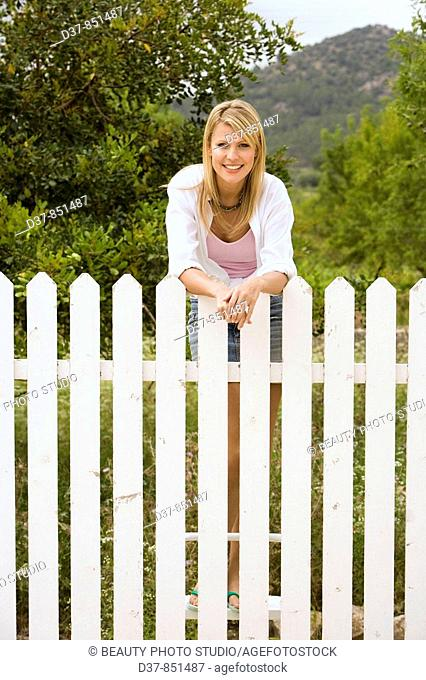 Woman standing behind a fence in the garden