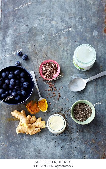 An arrangement of various superfoods (blueberries, cacao nibs, coconut oil, turmeric, ginger, plain yoghurt and chia seeds)