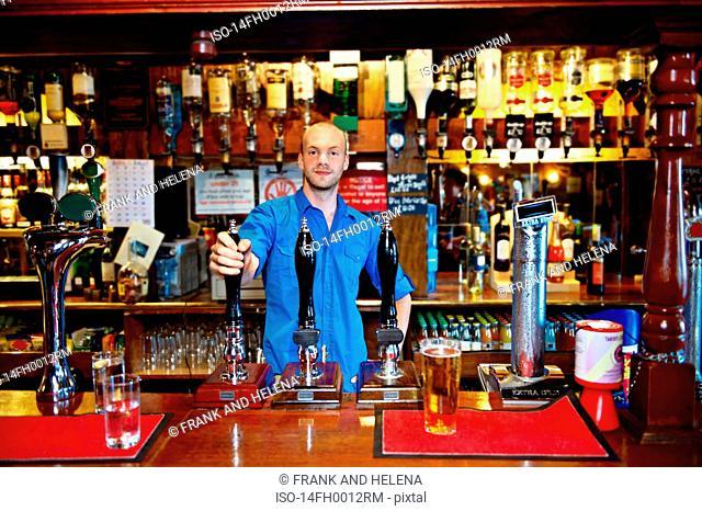Barman standing behind bar in pub