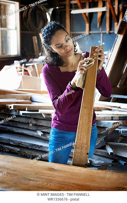 A woman working with reclaimed timber in a woodwork workshop