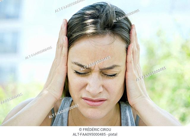 Distressed woman with head in hands