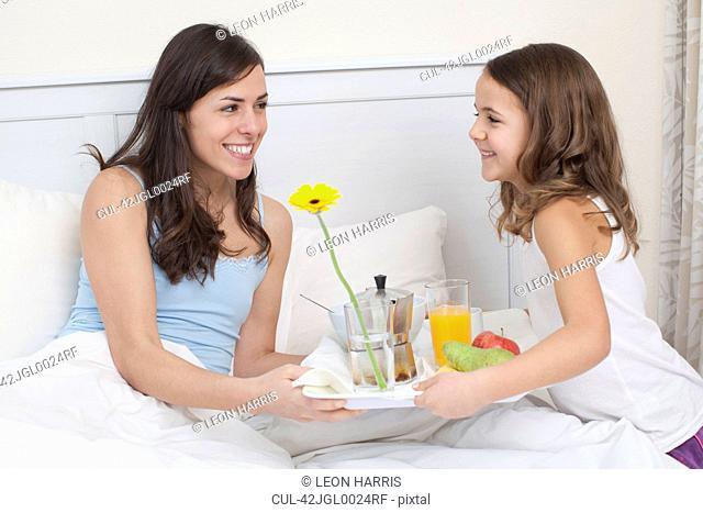 Girl bringing mother breakfast in bed