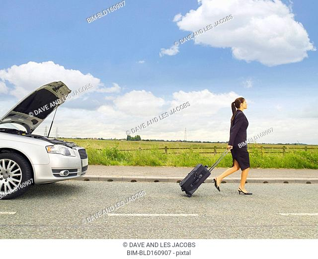 Caucasian businesswoman leaving broken down car on rural road