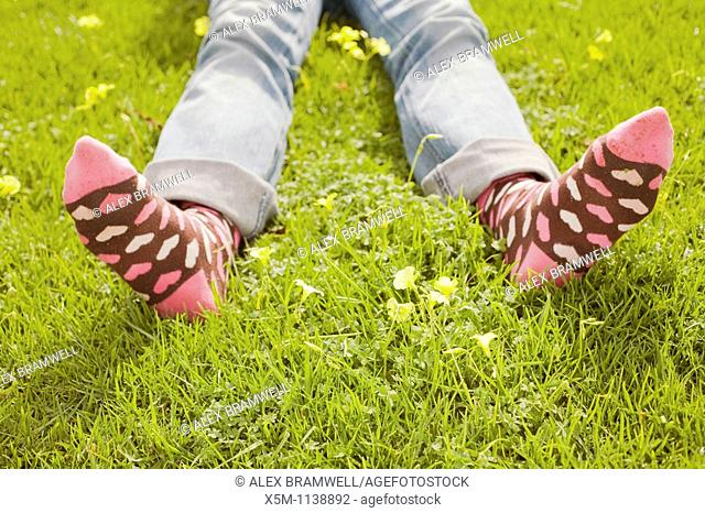 Woman on a green lawn with decorative socks