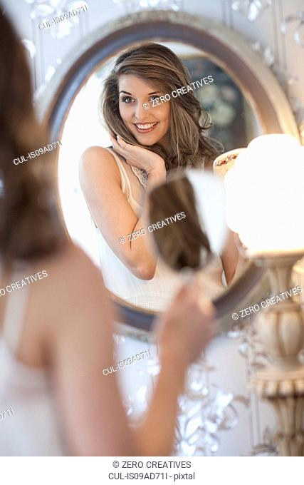 Portrait of young woman looking in wall mirror
