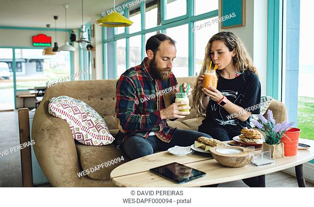 Couple having breakfast in cafe, drinking organic juices