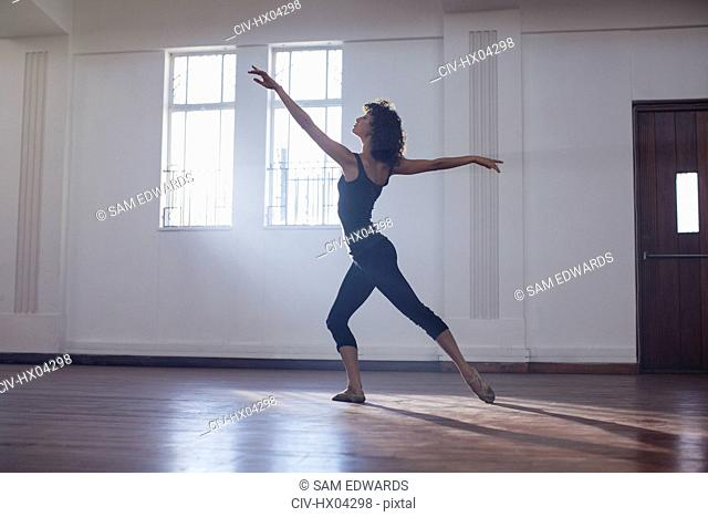 Graceful young female dancer practicing in dance studio