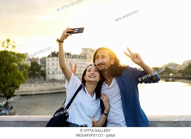 France, Paris, happy young couple taking a selfie at river Seine at sunset