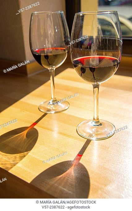 Two glasses of red wine and its shadow on wooden table