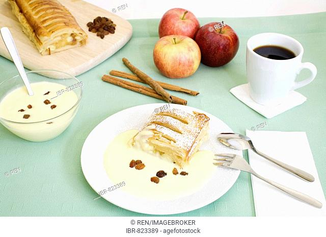 Apple strudel with vanilla sauce, cup of coffee and ingredients