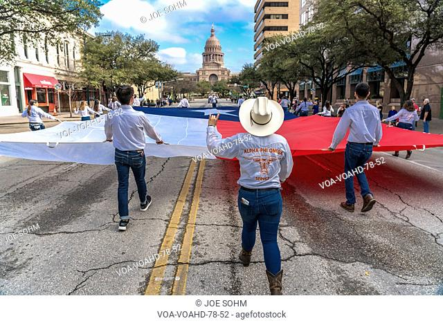 MARCH 3, 2018 - AUSTIN TEXAS - University of Texas students carry Texas flag down Congress Avenue for the annual Texas Independence Day parade to the Texas...