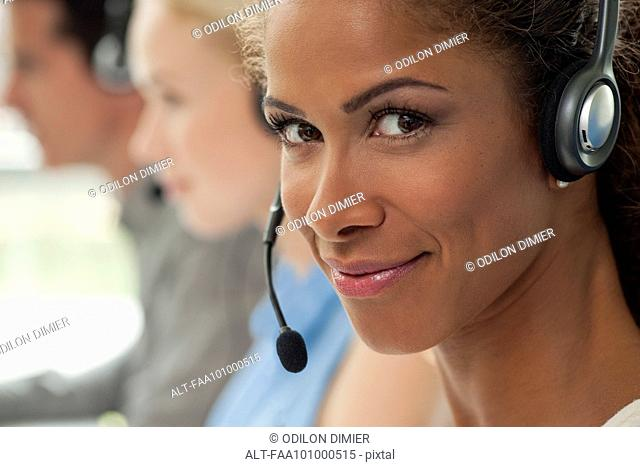Woman working in call center, smiling confidently