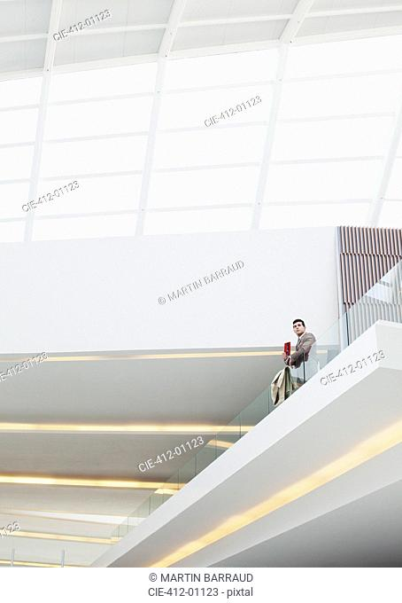 Businessman standing at glass balcony railing in modern building