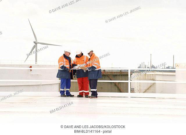 Caucasian technicians talking on fuel storage tank