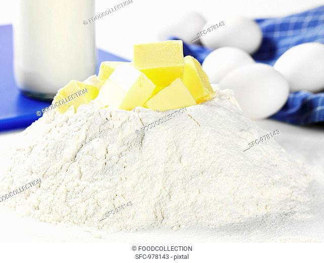 Heap of flour with cubes of butter