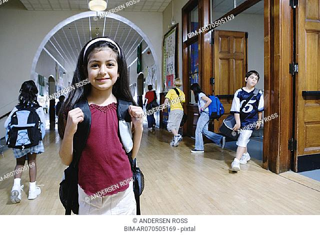 Girl in school hallway with students behind her