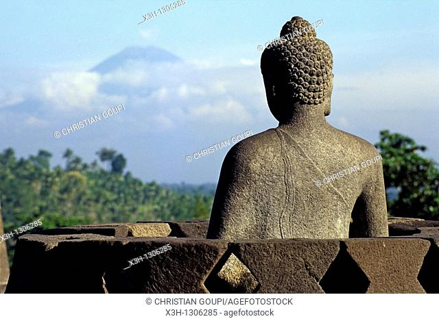 Buddha statue with the Merapi vulcano background, Borobodur Temple, Java island, Greater Sunda Islands, Republic of Indonesia, Southeast Asia and Oceania