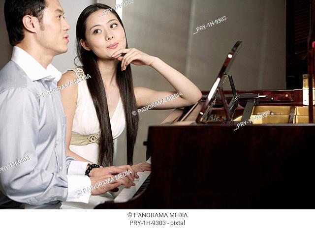 Young woman looking at man playing grand piano
