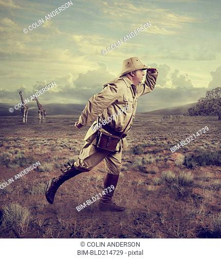 Hunter searching in remote savanna landscape