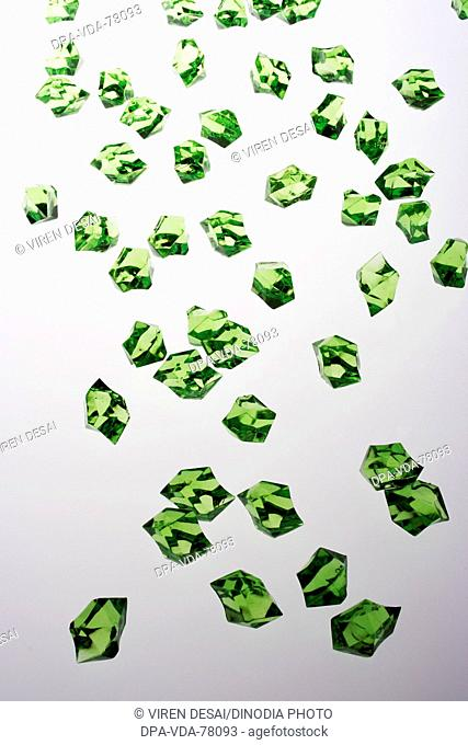 Many green colored acrylic pieces against white background