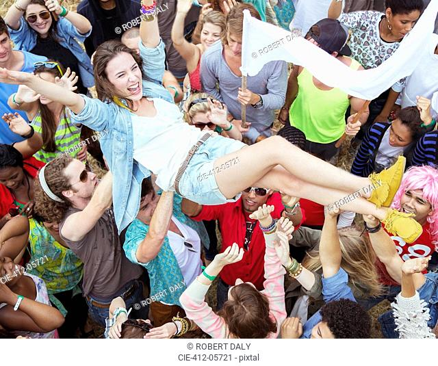 Woman crowd surfing at music festival
