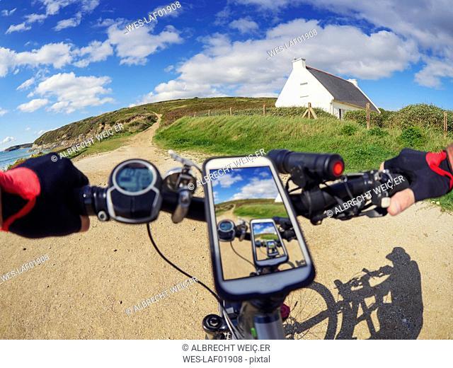 France, Bretagne, Sainte-Anne la Palud, Plage de Treguer, cell phone on mountain e-bike