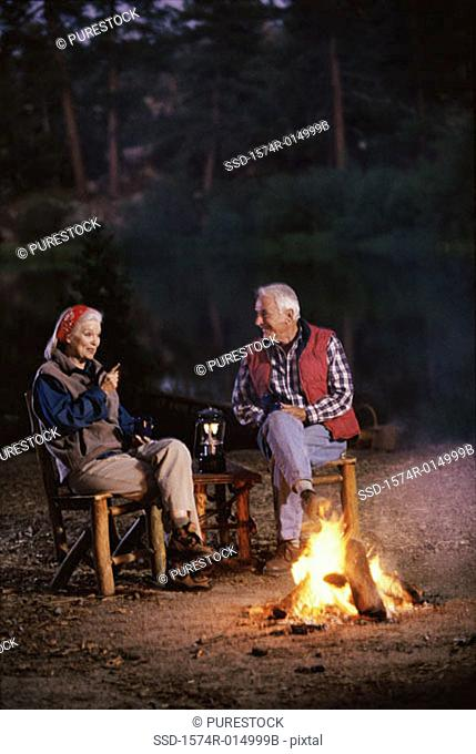 Senior couple sitting near a campfire talking to each other